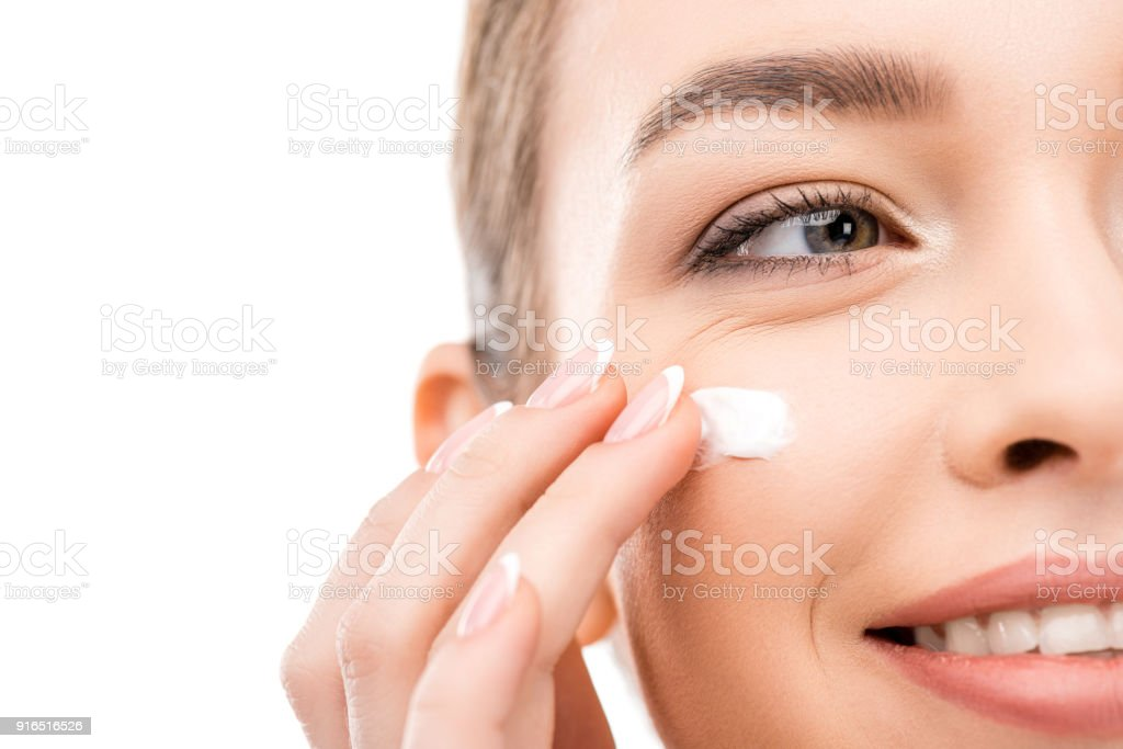 cropped view of young woman applying cosmetic cream, isolated on white stock photo