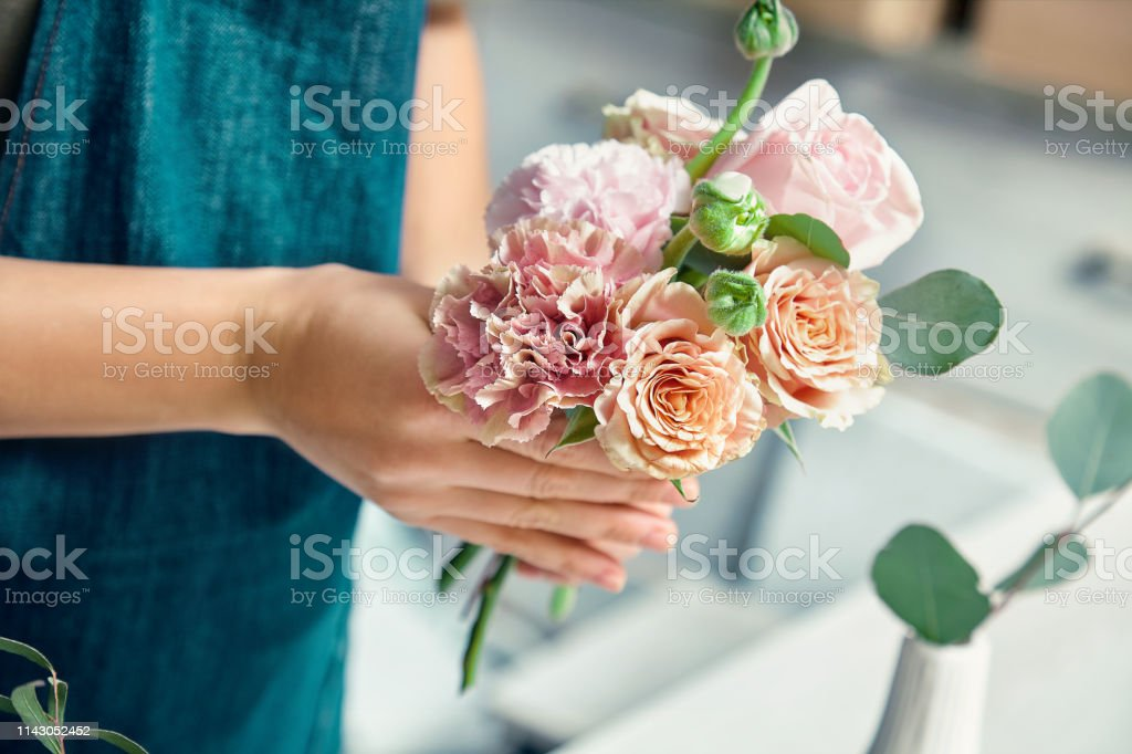 Cropped view on creative florist making flower bouquet in floral...