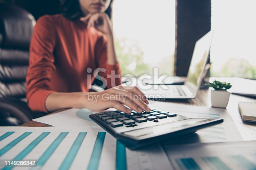 istock Cropped view photo of charming nice lady chief boss count trade calculate profit table desk think thoughtful ponder touch chin hand fingers wear style stylish trendy red pullover interior 1149286342