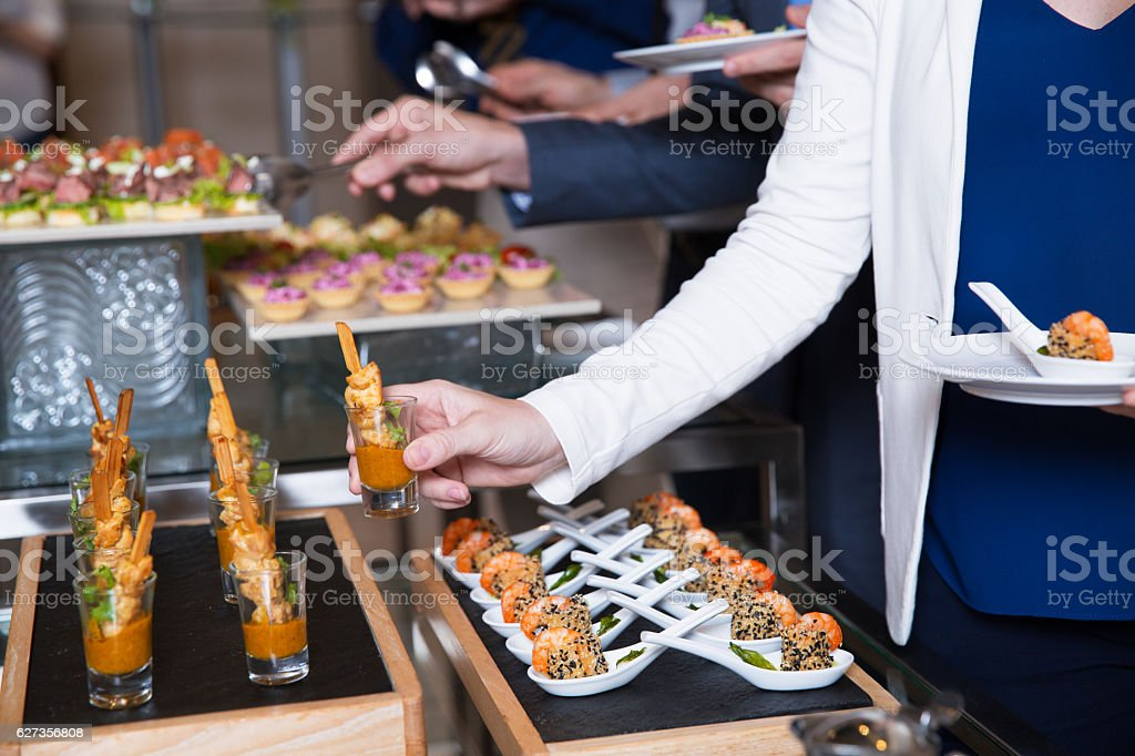 Cropped Woman Taking Snack from Buffet Table stock photo