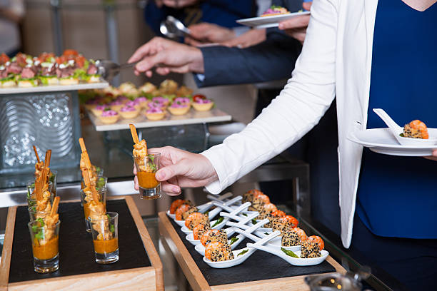 cropped woman taking snack from buffet table - party buffet stock-fotos und bilder