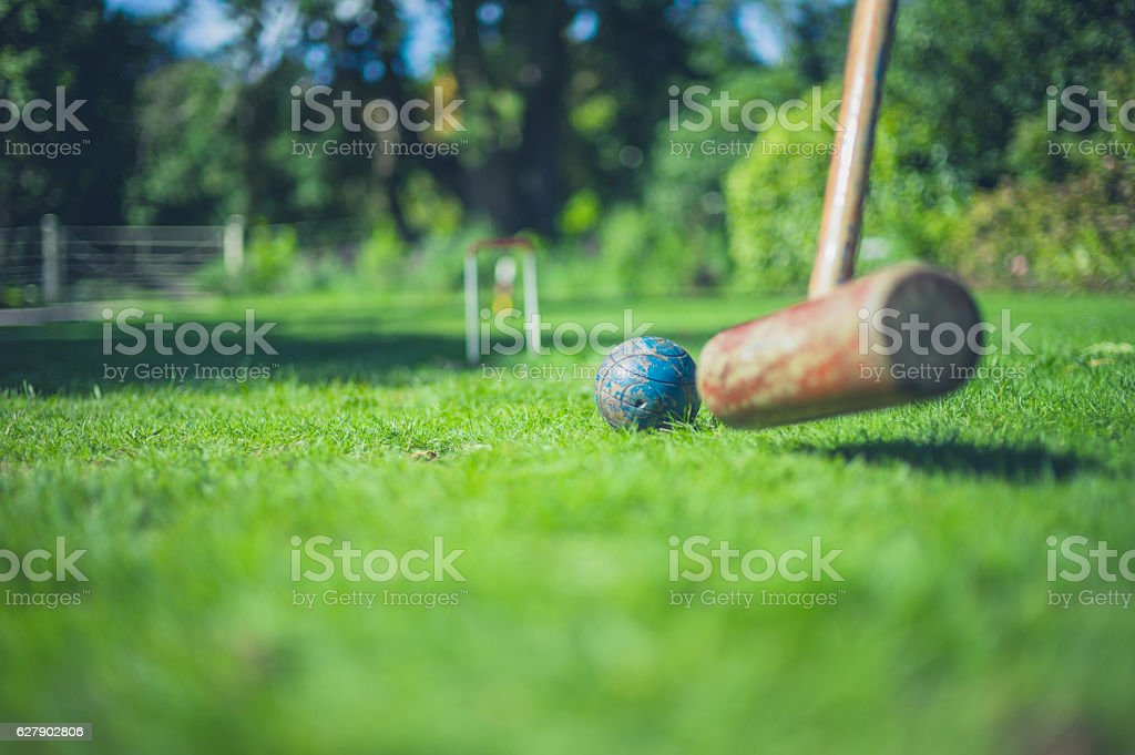 Croquet mallet hitting ball stock photo