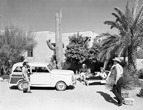 Tucson, Arizona, USA - March 31, 1948: Woman getting into a 1948 Crosley station wagon at Hacienda del Sol resort in the Sonoran desert near Tucson, Arizona. Resort guests relax while admiring the car. Scanned film.