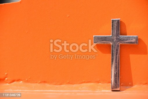 cross Against an orange wall