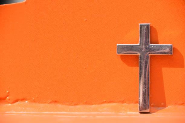 Kreuz gegen eine orangefarbene Wand – Foto