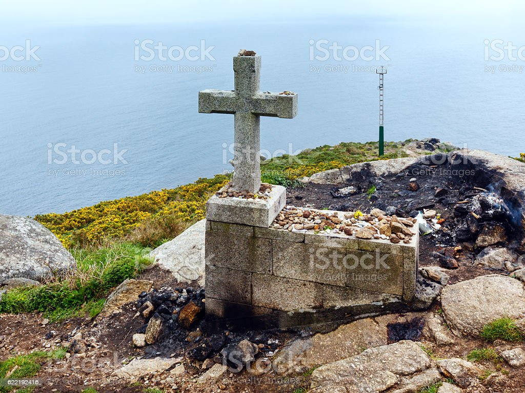Cross and fireplace on Cape Fisterra (Galicia, Spain). stock photo