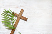 istock Cross and palm on wooden white background easter sign symbol concept 1129579339