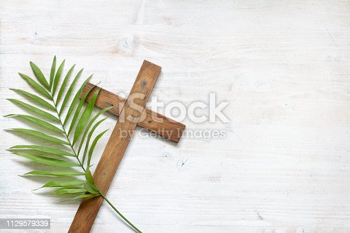 Cross and palm on wooden white background easter sign symbol concept ab stract