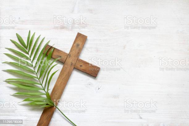 Cross and palm on wooden white background easter sign symbol concept picture id1129579339?b=1&k=6&m=1129579339&s=612x612&h=nzhlkxwqu9uq2alrsl7lau3qc4en6g5nsgx7pcibhve=