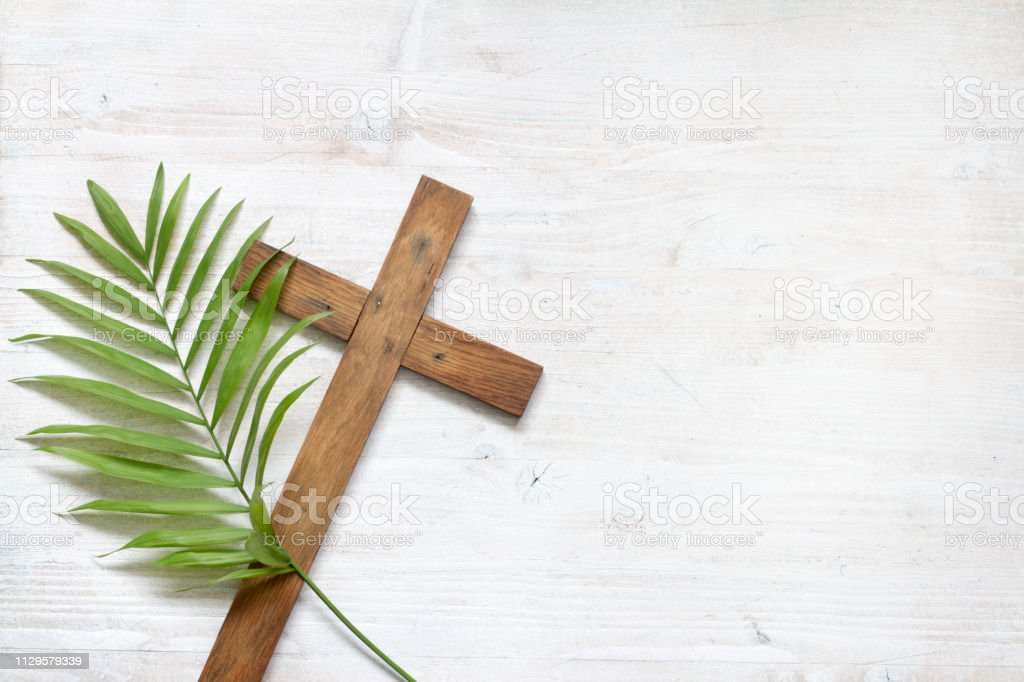 Cross and palm on wooden white background easter sign symbol concept stock photo