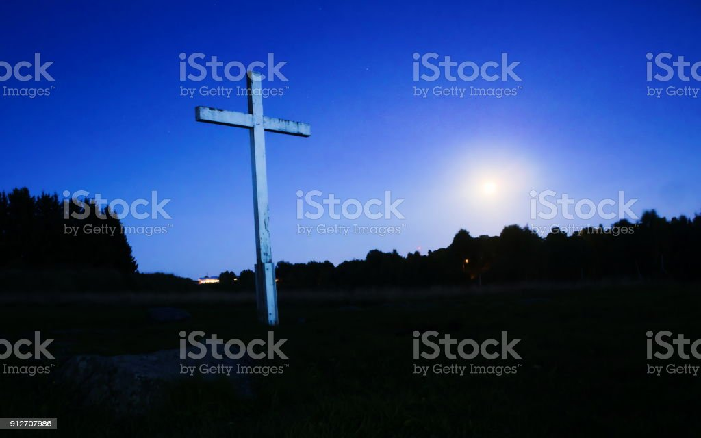 Cross at night against sky, moon in background stock photo