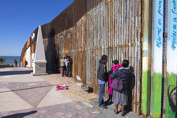 Cross border family meetings Playas de Tijuana, Mexico - January 28, 2017: Mexican families living in Tijuana visit with family members living in the United States by meeting at the border wall in Playas de Tijuana on a sunny winter Saturday morning. international border barrier stock pictures, royalty-free photos & images