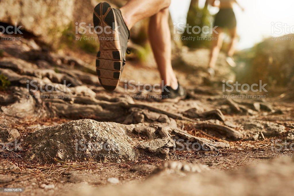 Cross country running. Closeup of male feet run through rocky...