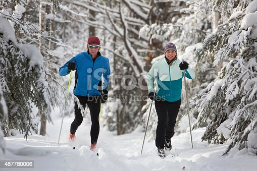 A man and woman cross country skiing on a snowy trail in the midwest.