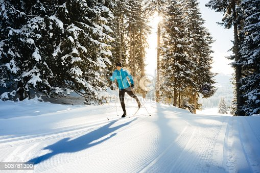 Backlit shot of a male athlete doing cross country skiing in the dolomite alps, northern Italy. Shot late in the afternoon against the sun