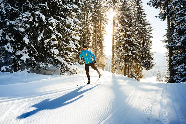 Cross Country Skiing Backlit shot of a male athlete doing cross country skiing in the dolomite alps, northern Italy. Shot late in the afternoon against the sun dolomites stock pictures, royalty-free photos & images