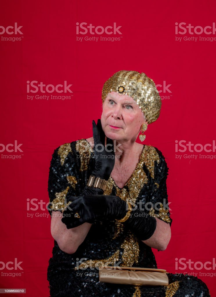 Cross dressed 70 year old man in gold and black lame. stock photo