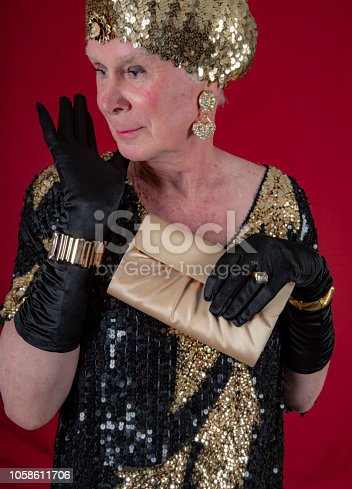 Cross dressed 70 year old man in gold lame dancing with purse.