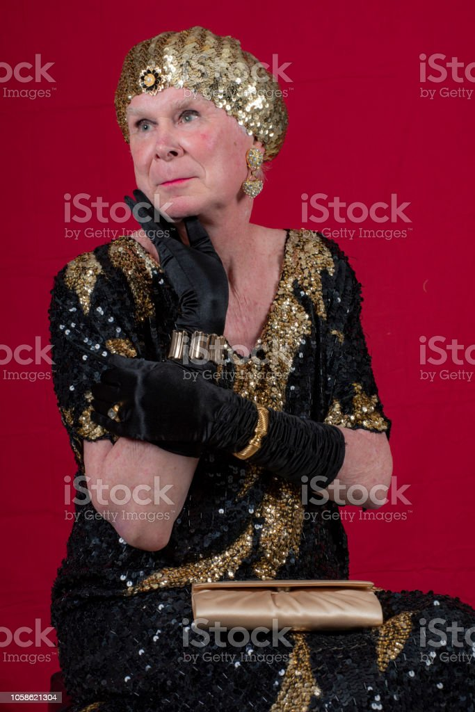 Cross dressed 70 year old man in gold lame preparing to go out with purse. stock photo