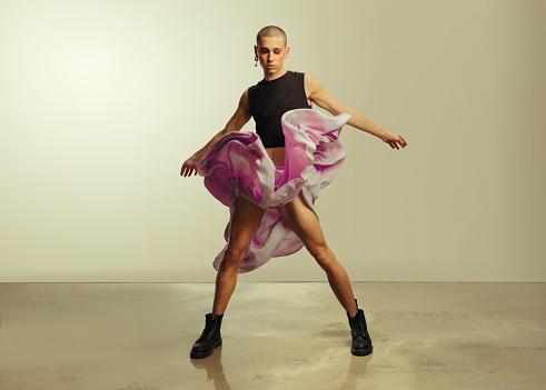 Gender fluid young man in crop top and skirt dancing in studio. Gay man dancing with his skirt flying.