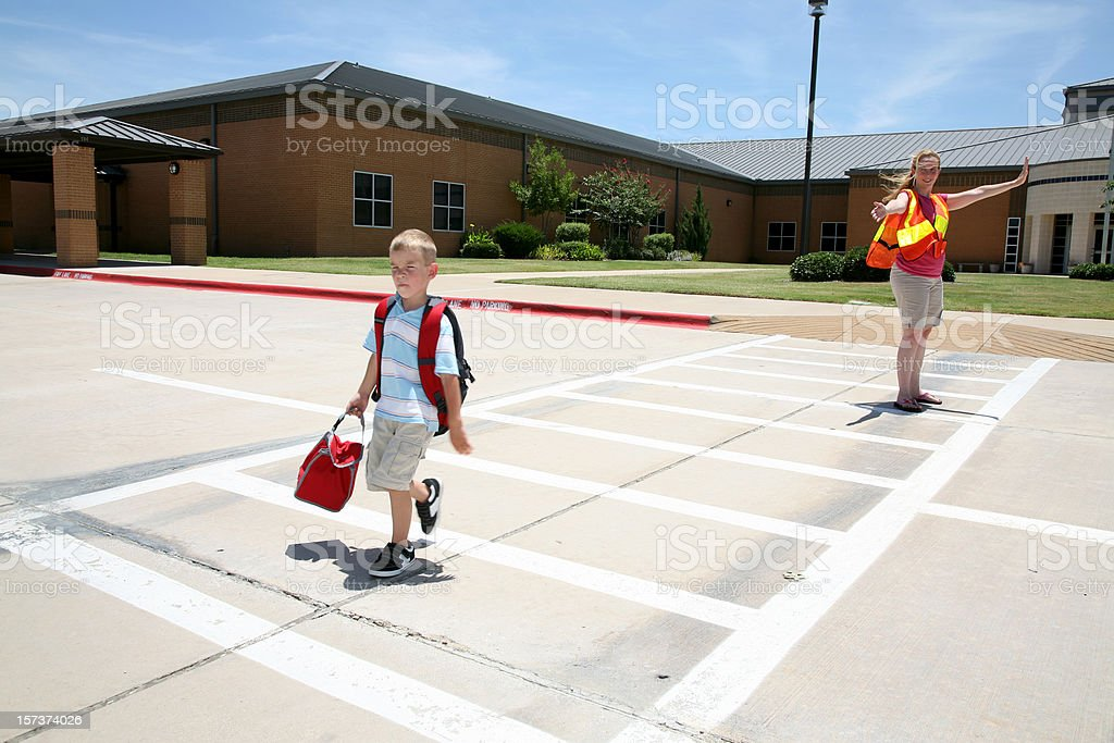 Cross Guard Helping Boy Walk Across The Street At School stock photo