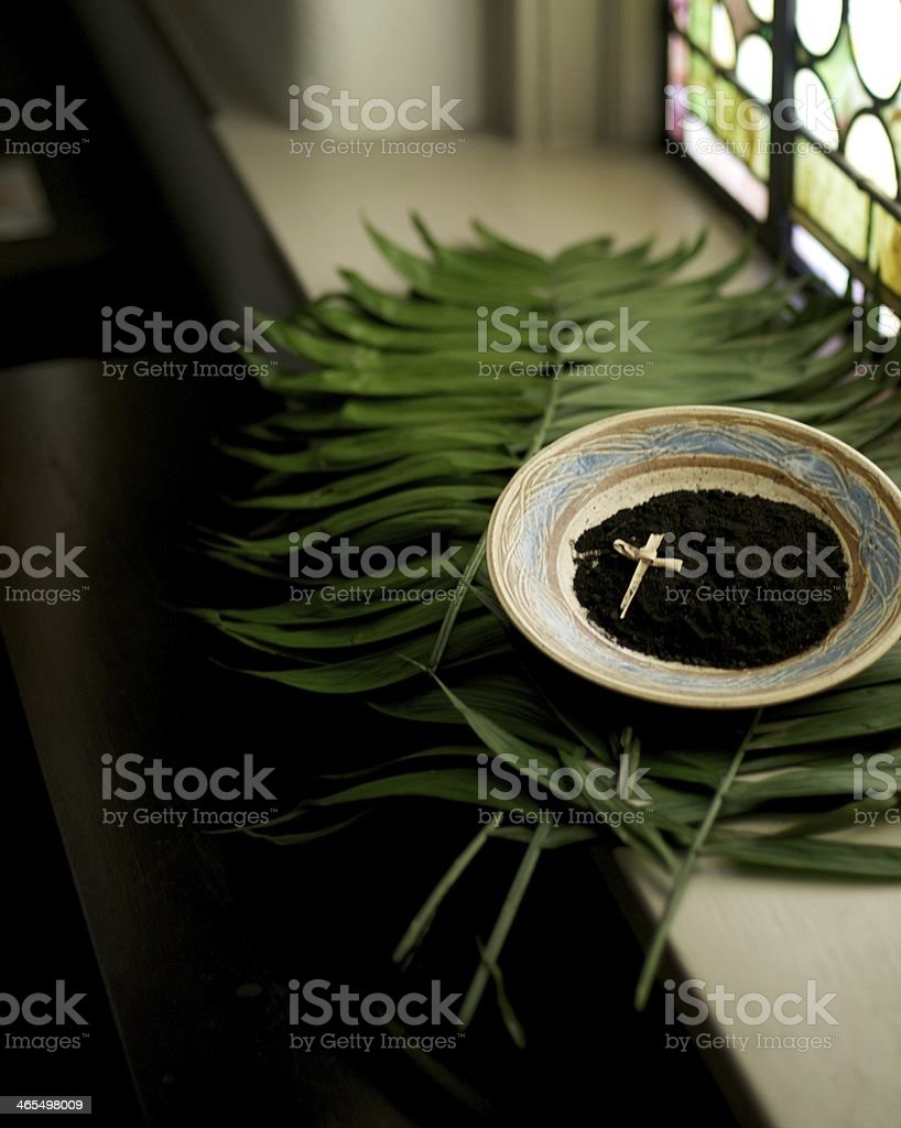 A cross in a bowl of dirt on top of leaves next to a window royalty-free stock photo