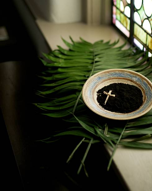 a cross in a bowl of dirt on top of leaves next to a window - ash cross stock photos and pictures