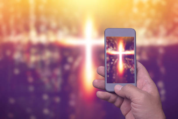 cross in screen mobile phone, spirituality religion online concept stock photo
