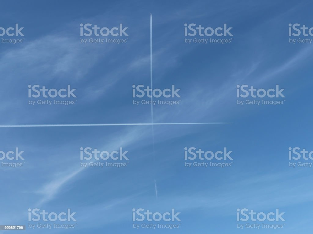 Cross in the blue sky. Two glowing bright tracks from flying in the blue sky of the plane intersect crosswise at a right angle of 90 degrees. stock photo