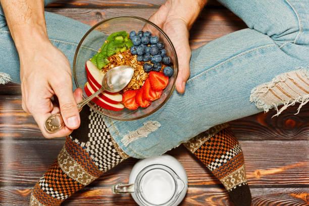 床で朝食を有する十字の脚の人 - ローフード ストックフォトと画像