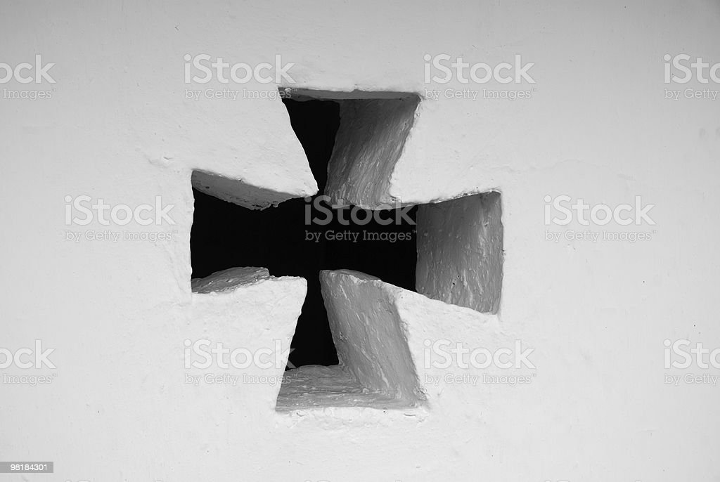 Cross loophole in the white wall royalty-free stock photo