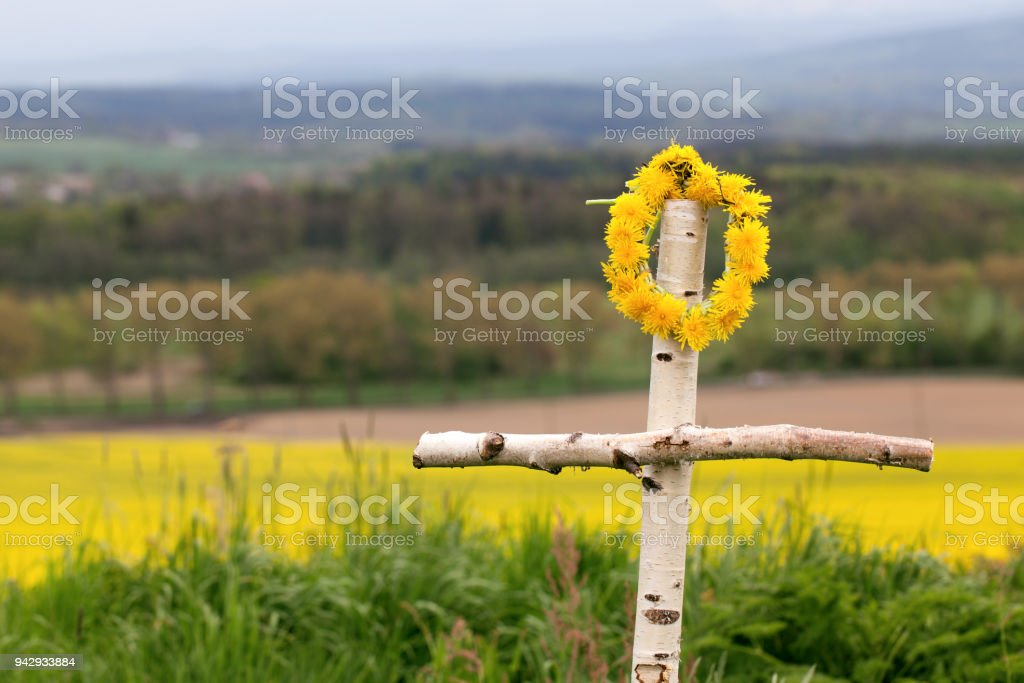 cross made of birch on the background of mountains and rape fields. Way of the Cross stock photo