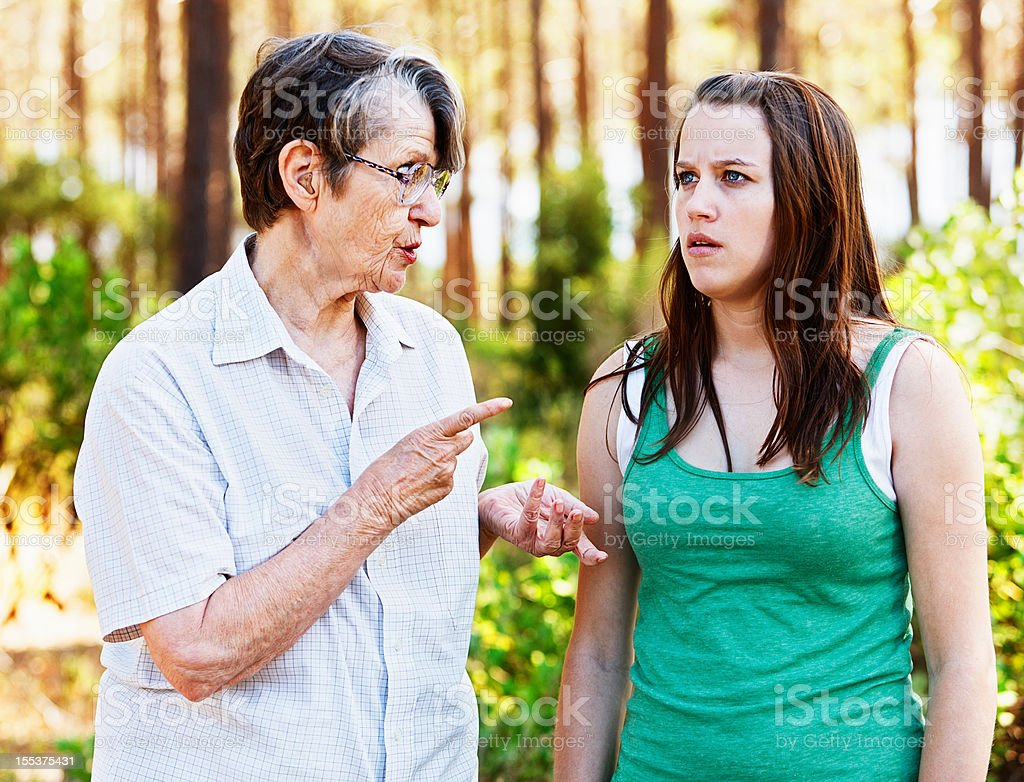 Cross old lady chastising sulky young woman: stock photo