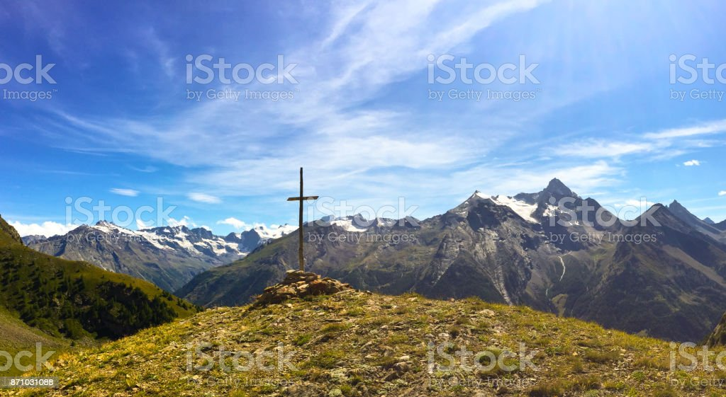 Cross on a mountain in front of Italian Alps stock photo
