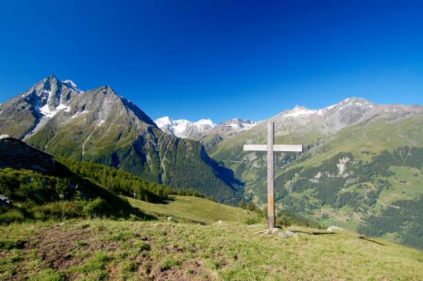 Cross on Hilltop in Alps stock photo