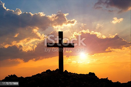 Cross on mountain sunset background. Easter concept. Concept conceptual black cross religion symbol silhouette in grass over sunset or sunrise sky.