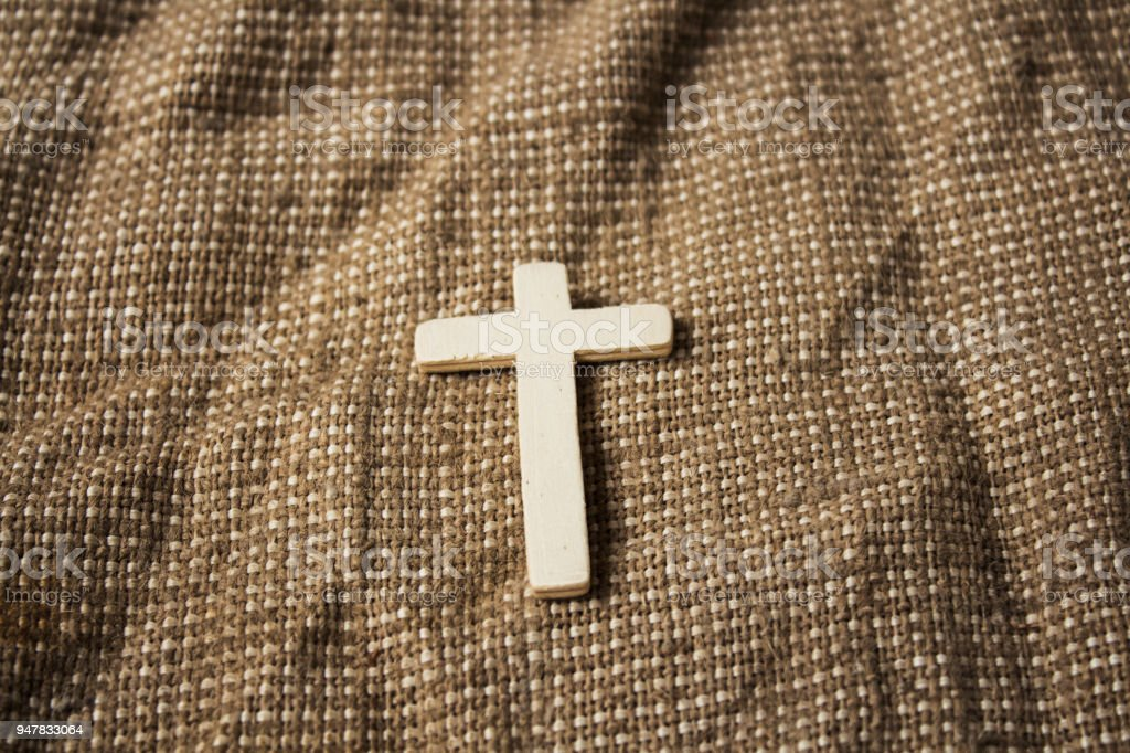 cross on sackcloth background stock photo