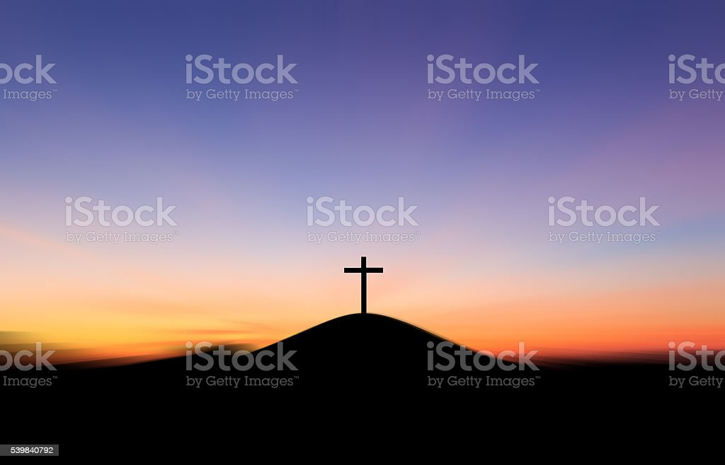Cross on the hill behind the blur sunset. stock photo