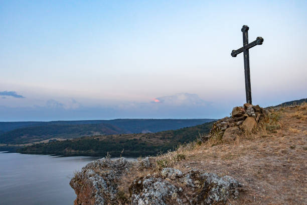 A cross on the rocks over Pchelina Reservoir in Bulgaria stock photo