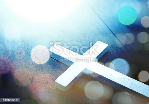istock Cross on wood and bokeh background 516646472