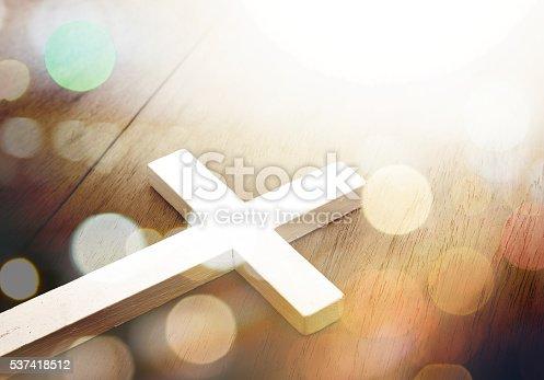 istock Cross on wood and bokeh background 537418512
