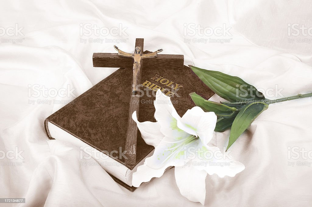 A cross resting on the Holy Bible next to a white flower royalty-free stock photo