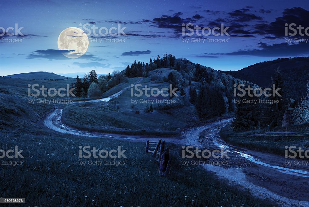 cross road on hillside meadow in mountain at night stock photo