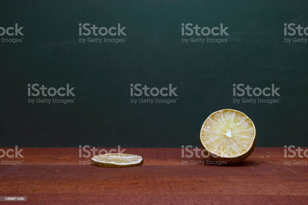 Cross Section Of A Lime And A Lime Slice On A Wooden Table. Green Background. Organic Accent To The Flavors Of Foods And Beverages. stock photo