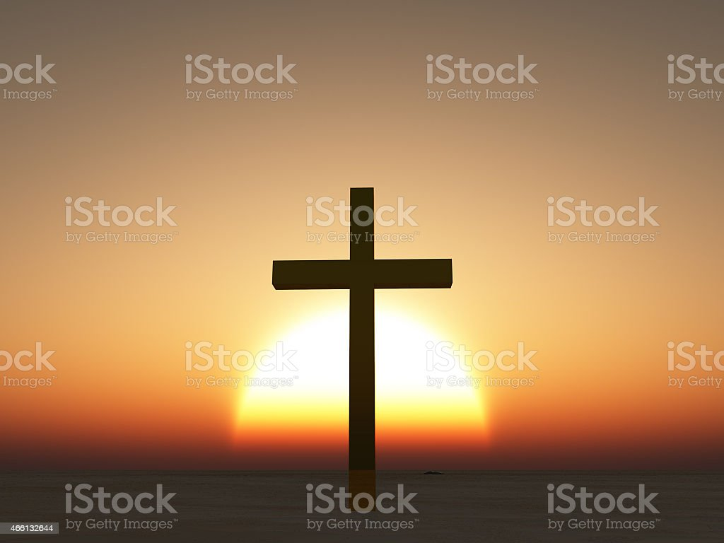 A cross standing against a sunset stock photo