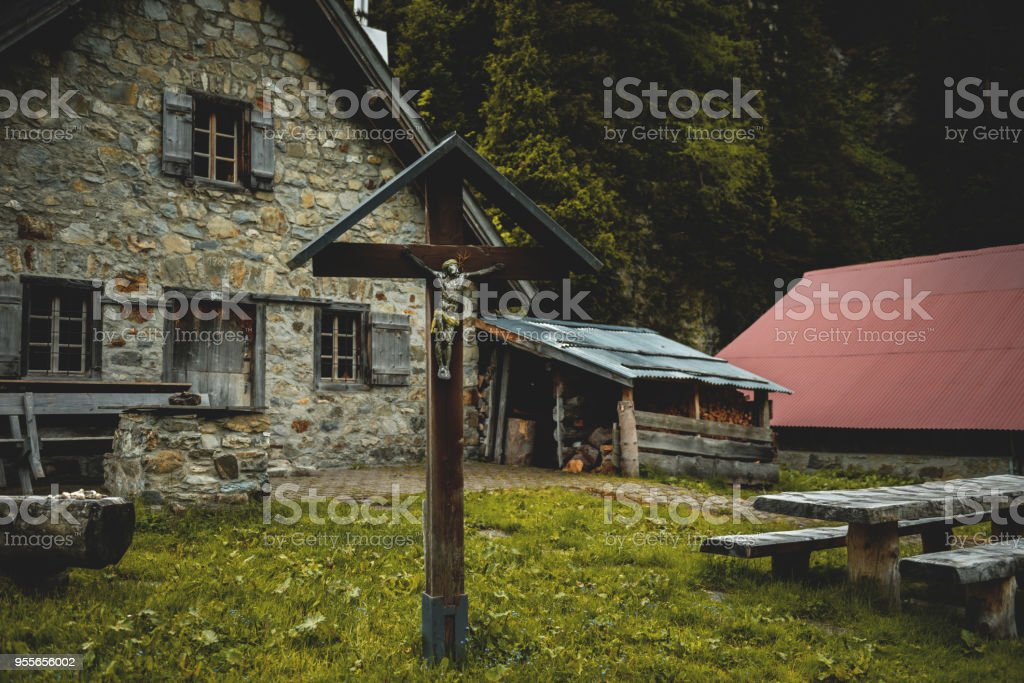 Cross statue in front of mountain chalet. stock photo