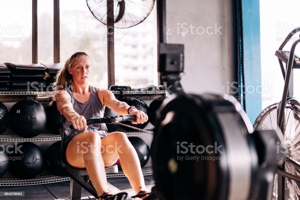 Cross training and rowing on the machine in gym - Royalty-free 20-29 Years Stock Photo