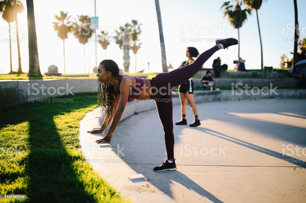 Vintage toned image of two young mixed race women doing cross...