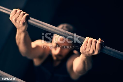 Male athlete performing chin-ups during cross training class in the gym.