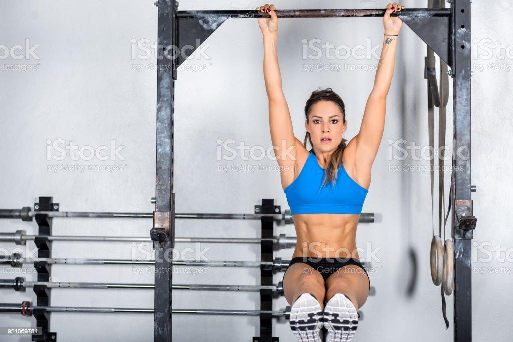 Atravessar o treinamento & mulher na barra de ginástica - foto de acervo